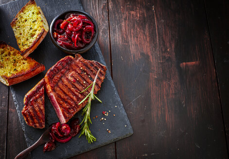 Beefsteak with rosemary, red wine onions and garlic bread on slate - KSWF01949