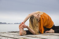 Mid adult woman touching toes practicing yoga on wooden sea pier - CUF38114