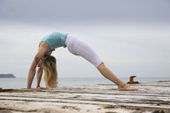 Mid adult woman bending over backwards practicing yoga on wooden sea pier - CUF38117