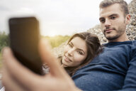 Attractive young couple posing for selfie on smartphone - CUF38147
