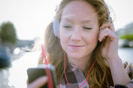 Close up of young woman listening to music on headphones on street - CUF38159