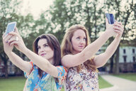 Two young female friends taking selfie on smartphones side by side - CUF38162