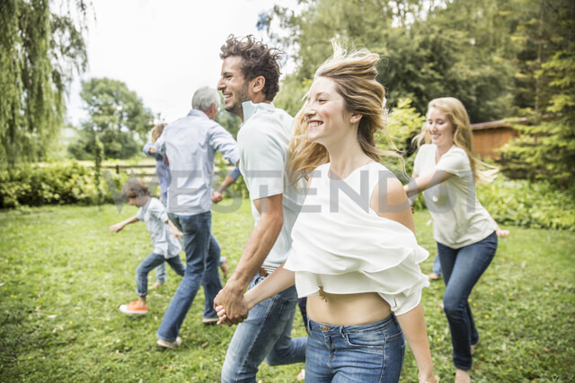 Young man and woman running in garden with family - CUF38204