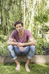 Young man sitting in garden - CUF38237
