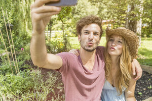Young couple taking selfie with cell phone in garden - CUF38240