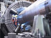 Engineers checking steel part in engineering factory - CUF38303