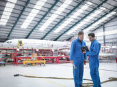 Engineers in discussion in aircraft maintenance factory - CUF38306