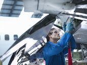 Engineer working on aircraft wing in aircraft maintenance factory, close up - CUF38318