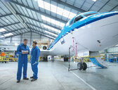 Engineers in discussion by aircraft in aircraft maintenance factory - CUF38321