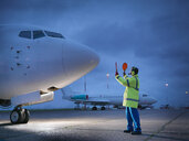 Airport worker guiding aircraft on runway at night - CUF38330