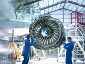 Aircraft engineers working on jet engine in aircraft maintenance factory - CUF38339