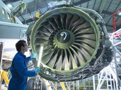 Engineer inspecting jet engine in aircraft maintenance factory - CUF38345