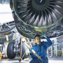 Portrait of engineer working on engine in aircraft maintenance factory - CUF38348