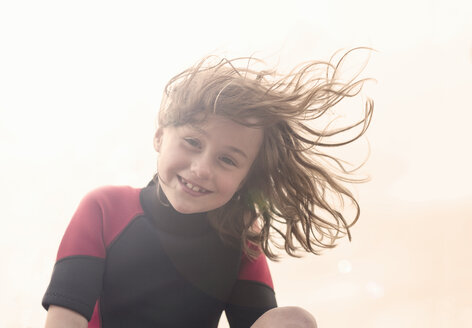 Girl wearing wetsuit looking at camera, smiling - CUF38579