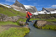 Hiker jumping over little river at Dyrfjoll Mountain range, East Iceland, Iceland - CUF38594
