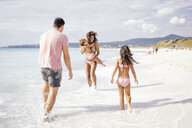 Couple and two girls playing on beach, Tuscany, Italy - CUF38603