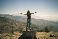 Rear view of mid adult woman on tree trunk with open arms, Lake Arrowhead, California, USA - ISF15381