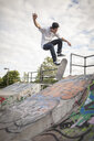 Young man skateboarding mid air in city skateboard park - ISF15396