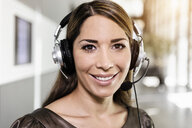 Portrait of mid adult businesswoman using telephone headset - ISF15426