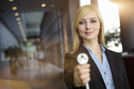 Portrait of young businesswoman holding up network power cable in office - ISF15447
