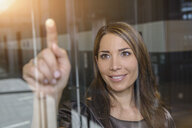 Businesswoman pointing out of glass window - ISF15453