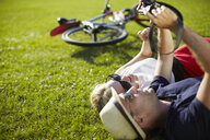 Couple lying in park looking at photographs on digital camera - ISF15567
