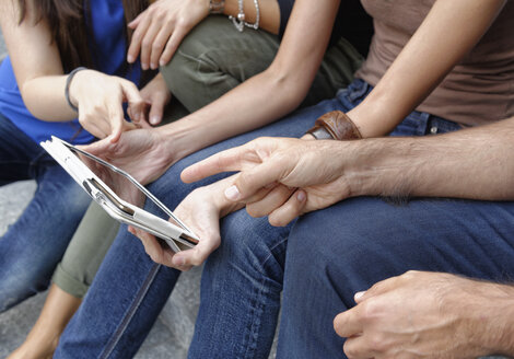 Group of friends looking at digital tablet, focus on tablet and hands - CUF38661