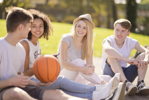 Four young adult basketball players sitting chatting - CUF38670