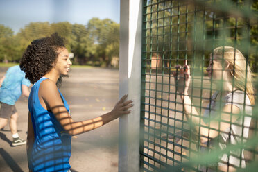 Two young female basketball players chatting on opposite wire fence - CUF38688