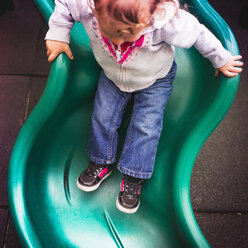Toddler going down slide in playground - ISF15636