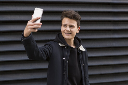 Portrait of smiling teenage boy taking selfie with smartphone in front of black background - JUNF01068