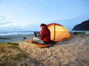 USA, Hawaii, Kauai, Polihale State Park, woman using laptop at tent on the beach at dusk - CVF00932