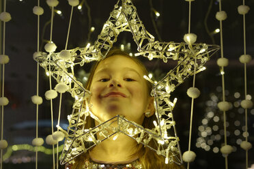 Portrait of smiling little girl looking through Christmas star - LBF01995