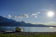 Germany, Bavaria, Upper Bavaria, Heimgarten, Kochelsee, boat and paddleboard at lakeshore against the sun - LBF02004