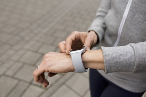 Woman's hand adjusting settings of smartwatch, close-up - JUNF01083