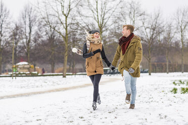 Happy young couple in love walking hand in hand in a park on snowy day - WPEF00569