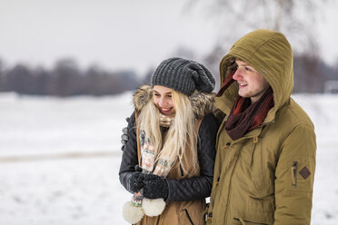 Happy young couple in park on a snowy day - WPEF00578