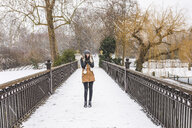 Teenage girl standing on footbridge in a park on a snowy day - WPEF00581