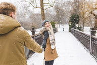 Portrait of happy teenage girl standing hand in hand with her boyfriend on footbridge on a snowy day - WPEF00584