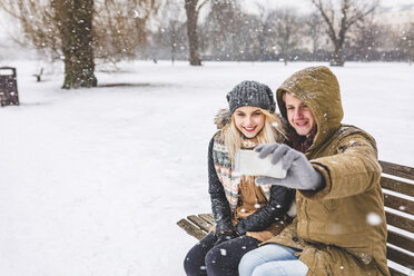 Happy young couple taking selfie with cell phone on snowy day in the park - WPEF00587