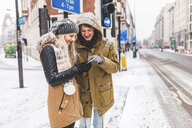 UK, London, young couple standing at roadside looking at cell phone on a snowy day - WPEF00590