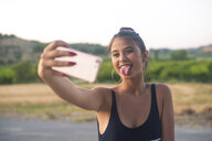 Portrait of teenage girl taking selfie with smartphone while sticking out tongue - ACPF00078