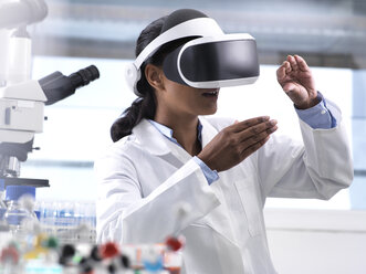 Female scientist using virtual reality to understand a research experiment in the laboratory - ABRF00159