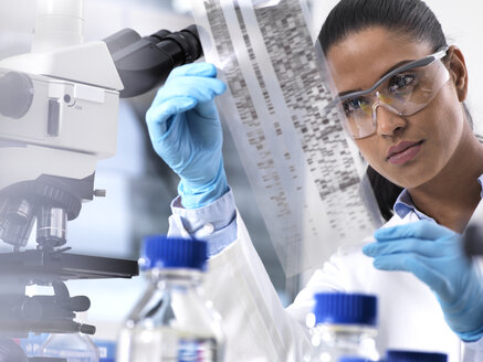Genetic Research, female scientist holding a foil with genetic code, the genetic make-up - ABRF00177