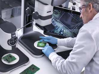 Engineer using a 3d stereo microscope for quality control in the manufacturing of circuit boards for the electronics industry - ABRF00180