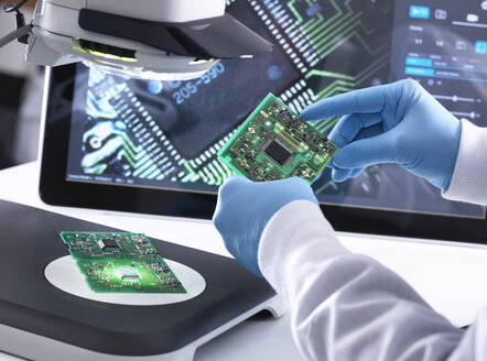 Engineer using a 3d stereo microscope for quality control in the manufacturing of circuit boards for the electronics industry - ABRF00183