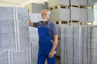 Factory worker moving and stacking cardboard - CUF38776