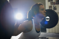 Woman lifting barbell in gym - CUF38785