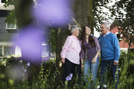 Grandparents and granddaughter standing by tree - CUF38833