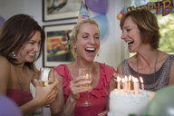 Three mature women at birthday party, laughing - ISF15708